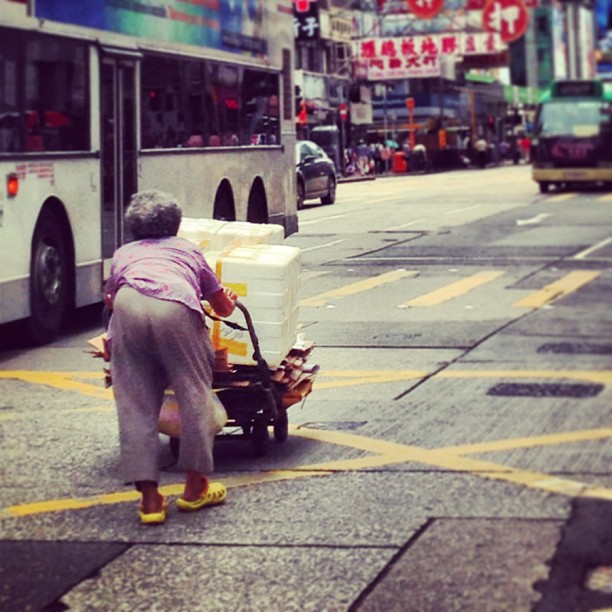 An-hunched-old-lady-pushes-her-cart-of-recyclables-hongkong